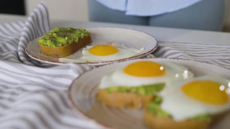 poached egg : Woman puts fried eggs on a plate with avocado toast. Healthy vegan breakfast. Stock Footage