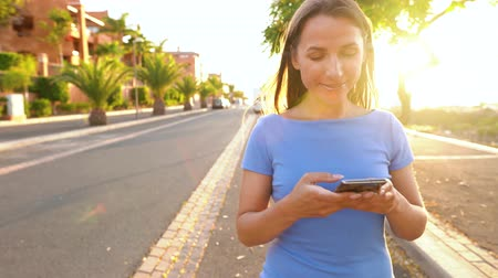 nerd : Woman in a blue dress using smartphone while walks on a palm street at sunset Stock Footage