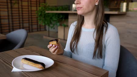 olejnatý : Woman eats chocolate eclair in a cafe