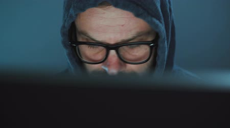 włamywacz : Male hacker in the hood and glasses working on a computer in a dark office room. Cybercrime concept
