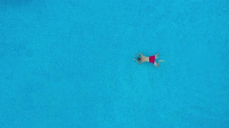 plongeons : View from the top as a man swims under the water in the pool. Slow motion