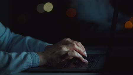 inputting : Woman is typing on a laptop at night