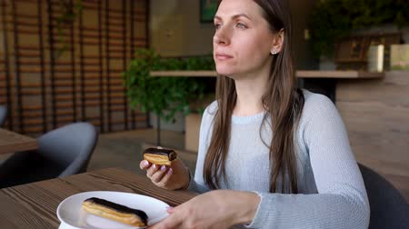 olajos : Woman eats chocolate eclair in a cafe