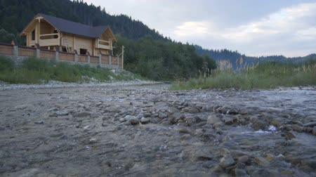 residencial : A mountain river flows along the forest and a lovely wooden house