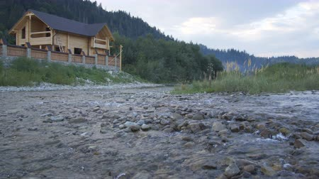 A mountain river flows along the forest and a lovely wooden house