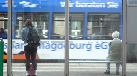 Girl and man waiting for a transport at bus stop, Magdeburg, Germany. 30.09.2018