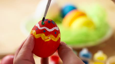 koszyk wielkanocny : easter, holidays, tradition and people concept - close up of woman hands coloring easter eggs with colors and brush