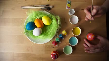 easter : Preparing for a happy Easter. Painted Eggs lying on the green plate next to brushes and paint on a wooden table.Female hand Paints Easter Egg with a Brush