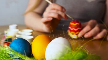 koszyk wielkanocny : Preparing for a happy Easter.A young Woman Paints Easter Egg with a Brush on the background of Wooden Table.by refocusing