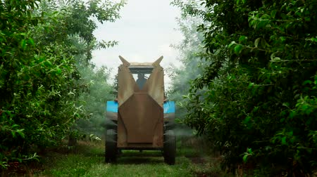 pulverização : A Rear view of the Fan Sprayer applying Chemicals in an Apple orchard. Stock Footage