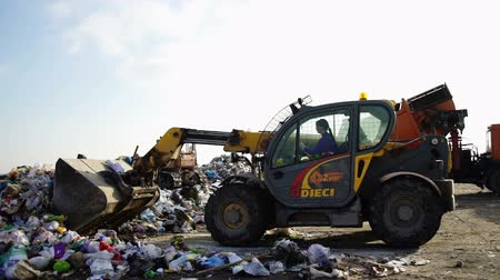 hijenik olmayan : RUSSIA - CIRCA 2017: A woman is driving a bulldozer in a dump.Bulldozer moves non biodegradable garbage at landfill
