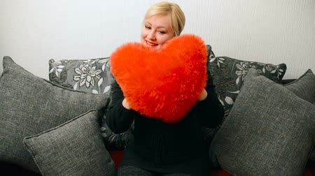 açoitado : Blonde woman with red pillow heart shaped. Saint Valentine and International Womens Day, Eight 8 March celebration. Stock Footage