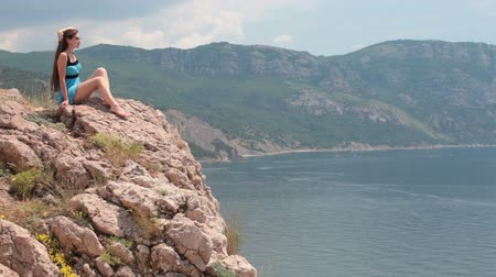 cliff : Woman sitting on the edge of a cliff Balaklava, Crimea, Ukraine