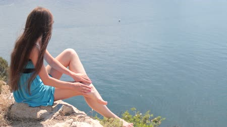 ayaklar : barefoot young woman resting on top of a mountain by the sea