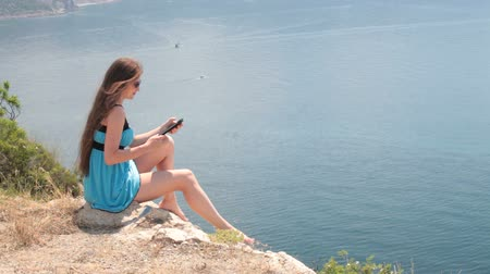 ler : woman reading e-book by the sea