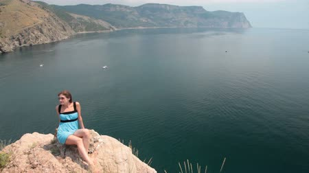 Украина : young woman Resting on the cliff near the Black Sea, Bay of Balaclava, Crimea