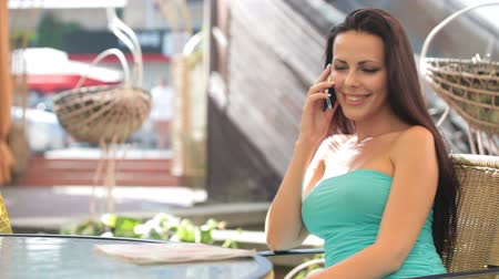 falar : woman talking on a cell phone while sitting in a cafe