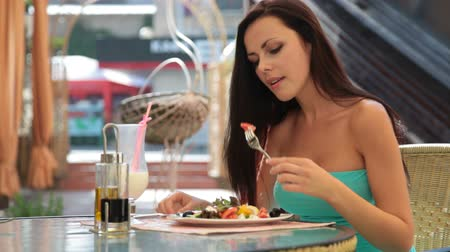 наслаждаться : young woman having dinner at a restaurant