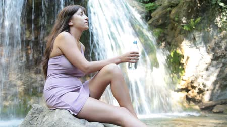 menő : young woman drinking water near the waterfall