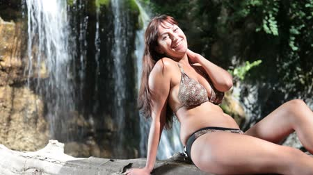 jovens : woman in bikini sunbathing near a waterfall
