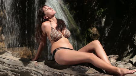 релаксация : Woman in bikini relaxing by  waterfall