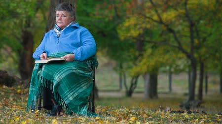 nadváha : Senior woman reading outdoors