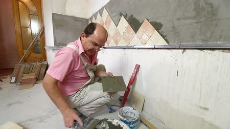 tynk : man installs ceramic tile