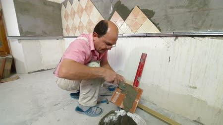 шпатель : man installs ceramic tile