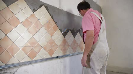 çini : man applying ceramic tile to a Kitchen wall, working with trowel