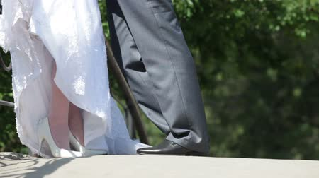 nogi : feet of bride and groom standing hugging on bridge Wideo
