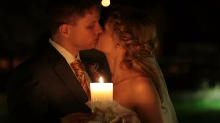 romantic couple : just married couple kissing by candlelight