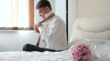 suit and tie : groom tying his tie preparing for the wedding ceremony