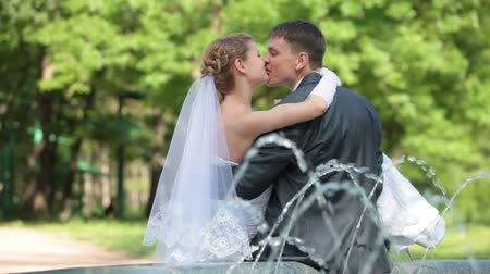 weddings : just married couple sitting near fountain