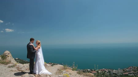 weddings : bride and groom on a cliff against blue sky