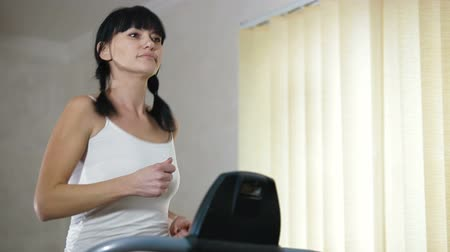 máquina : woman running on a treadmill at home Stock Footage