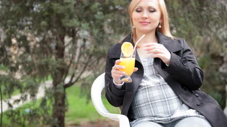 kobieta w ciąży : Pregnant woman drinking orange juice while sitting outdoors