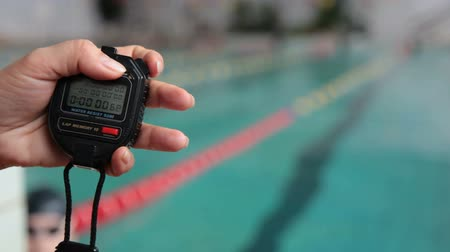 yarışma : hand of coach with a stopwatch during competitions in the swimming pool