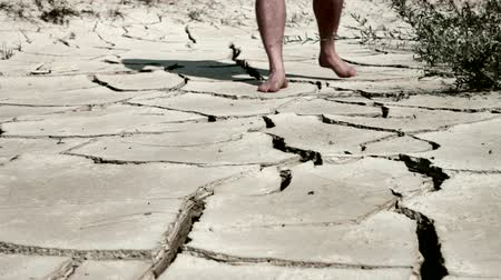 засуха : man`s feet on cracked desert earth
