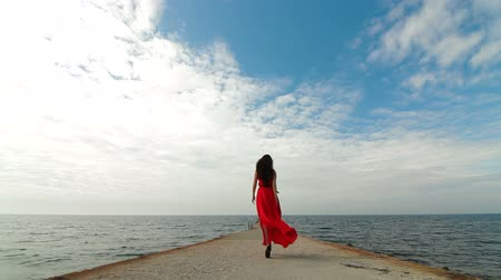 giydirmek : Woman In Red Dress Walking Down Pier