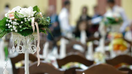 eleganckie : Flower arrangement on the wedding diner table in the background guests