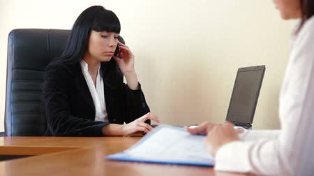 boss : Female manager talking on the phone not paying attention to the visitor