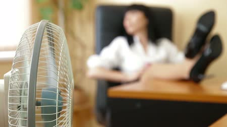 вентилятор : Relaxed Businesswoman With Feet On Table Focus On The Fan