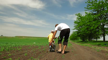sport dzieci : Father helping child learn to ride a bike