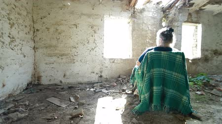 yoksulluk : An elderly woman looking out the window abandoned house, dolly shot
