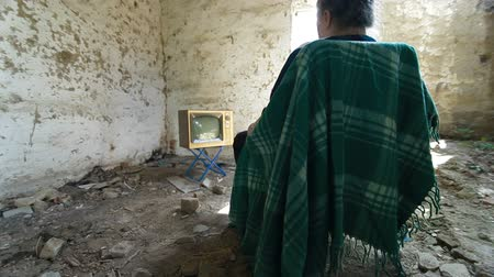 abandoned old : Senior Woman Watching Old TV In An Abandoned House, Dolly Shot, Rear View Stock Footage