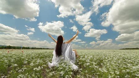 özgürlük : Attractive young woman sitting in a white blossoming field with her arms spread widely