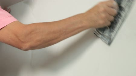 ceilão : Man sanding plaster on a new drywall installation, close-up Stock Footage