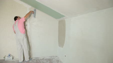 ceilão : Man applying plaster on a new drywall installation, long shot