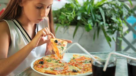 kind : Meisje eet pizza in een fast food restaurant