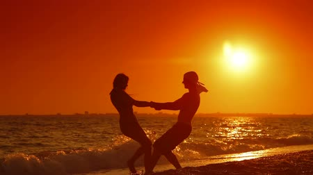 estância turística :  Young Couple  Spinning On The Beach at Sunset